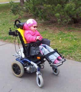 Holčička na elektrickém vozíku